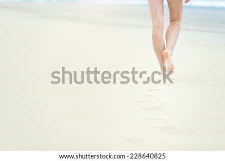 Young slim woman in white swimsuit walking to sea or ocean leaving footprints on soft sand. Blue ocean waves with foam in background. Bathing or sunbathing on beach. Holidays and vacations in summer. #228640825