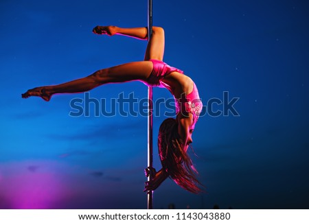 Young slim woman pole dancing at night on dark blue sky background #1143043880