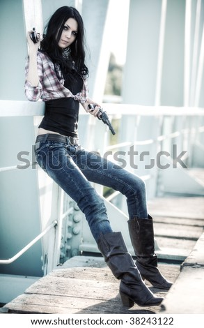Young slim woman with guns on a bridge.