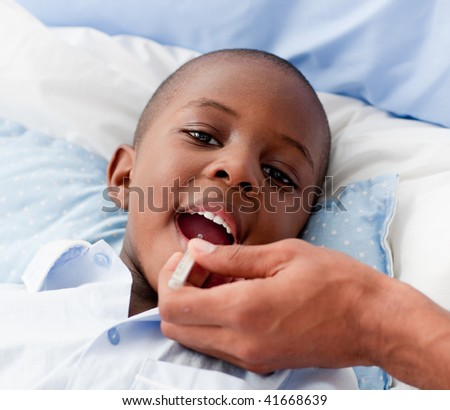 Young Small Boy sick in bed with the flu
