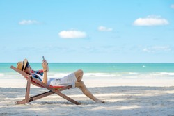 Young smart Asian man tourism in sunglasses relaxing and lying on beach chair on tropical island beach using smartphone with internet for working or online shopping in summer holiday vacation trip.