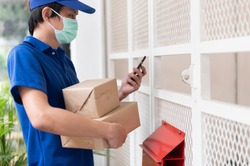 Young smart Asian package delivery service company staff wearing face mask prevent coronavirus checking customer information or address from smartphone before sending during covid-19 virus outbreak.
