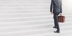 Young Smart Businessman walking up the stairs with copy space banner background.Concept of success business step.