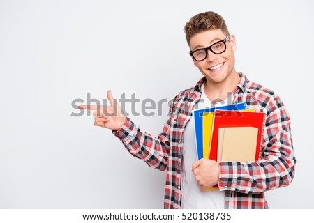 Young smart happy student with books pointing on copy space.