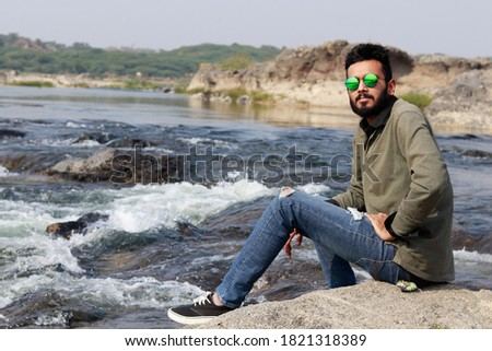Young Smart Indian Man sitting at River Side, looking at the camera Stockfoto ©