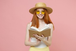 Young smart intelligent redhead cute smiling student woman 20s ginger wear straw hat glasses summer clothes holding reading interesting book isolated on pastel pink color background studio portrait