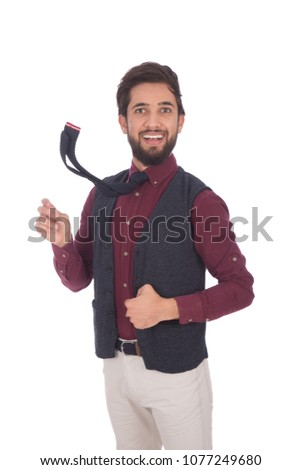Young smiley man wearing vest and shirt moving the necktie he wears make it fly, isolated on a white background. #1077249680