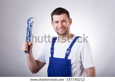 Young smiley repairman holding wrench in hand
