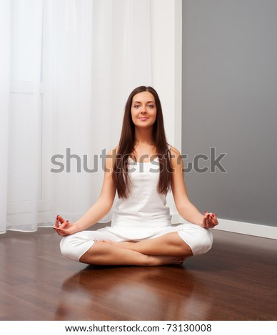 young smiley woman doing yoga in room