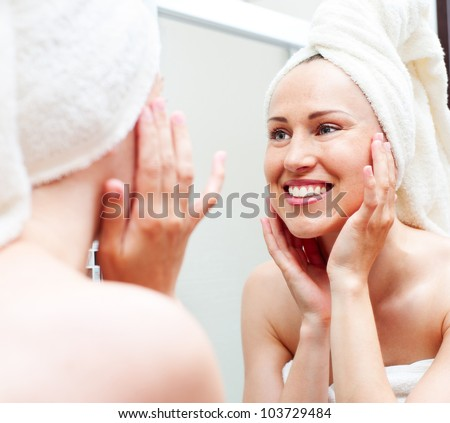 young smiley woman in towel looking in mirror