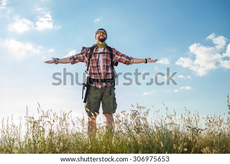 Young smilimg caucasian tourist with backpack  standing on the top of hill against blue sky #306975653