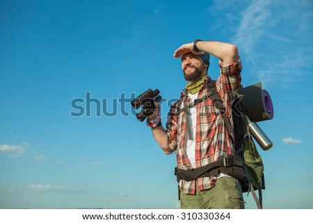 Young smilimg caucasian tourist with backpack  standing on the top of hill against blue sky background and looking through binoculars #310330364