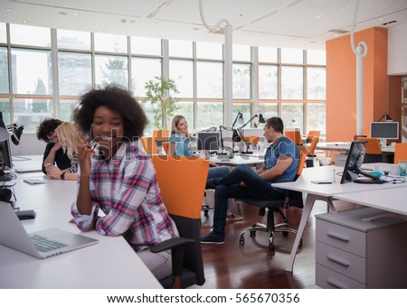 young smiling African American informal businesswoman working in the office with colleagues in the background #565670356