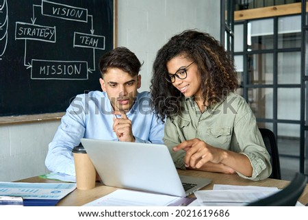 Young smiling African American mentor explaining to serious Indian coworker project strategy. Diverse startup coworkers students girl and guy talking discussing working in modern office using laptop.