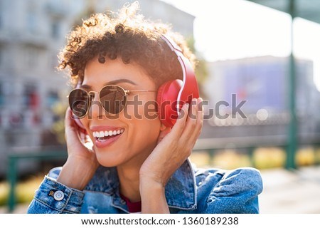 Young smiling african woman listening music with headphones at sunset. Brazilian girl listening songs via wireless headphones. Closeup face of teen wearing sunglasses and keeps the rhythm of the song.