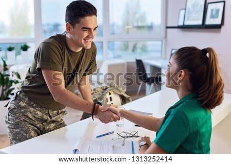 Young smiling army soldier meeting with his therapist and shaking hands while having a meeting at doctor's office.