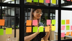 Young smiling asian business woman mentor leader write tasks creative ideas on sticky post it notes on glass wall, vietnamese female coach planning project corporate management on sticker scrum board