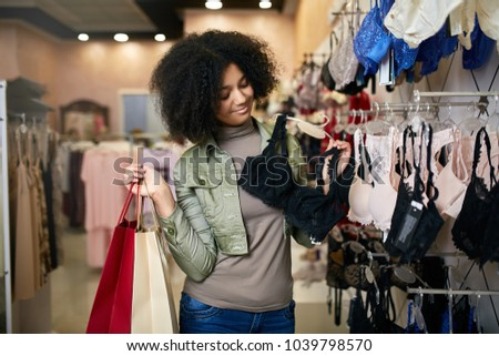 Young smiling attractive african american woman choosing right bra size in lingerie store boutique. Black mixed race pretty girl considers underwear in shop and holding paper shopping bags.