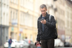 Young smiling attractive man with luggage bag walking in the rainy city street looking at smartphone, using app, gps, searching for direction, texting, making call, traveling, wearing casual clothes