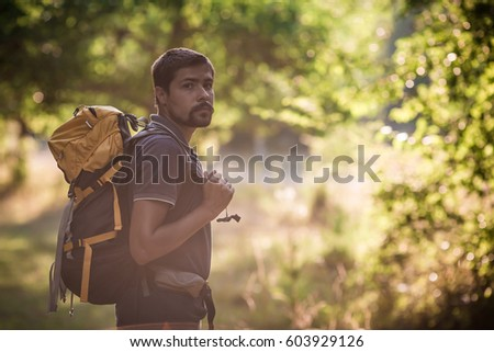 Young smiling backpack man in summer forest nature. Happy handsome male adult student looking at camera walking hiking in forest background. School bag or backpacking travel concept. #603929126