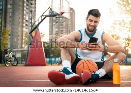 Young smiling basketball player using mobile phone while taking a break from sports activity outdoors. Urban basketball court background at sunset. Street life.