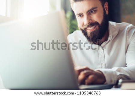Young smiling bearded businessman sitting in office at table, using laptop. Man works on computer, checks e-mail, planning, chatting, blogging. Online marketing, education, social network, e-learning.