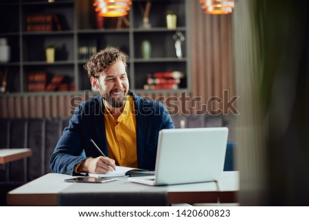 Young smiling bearded Caucasian blogger dressed smart casual writing notes in agenda and looking at laptop while sitting in cafeteria.