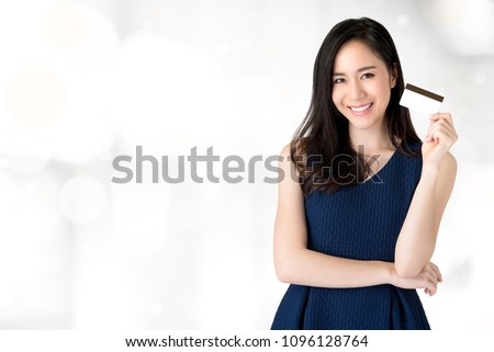 Young smiling beautiful Asian woman presenting credit card in hand showing trust and confidence for making payment
