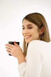 Young smiling beautiful happy woman with long hair enjoying cappuccino on white background. Beauty Woman enjoying Coffee. Cup of Hot Beverage.