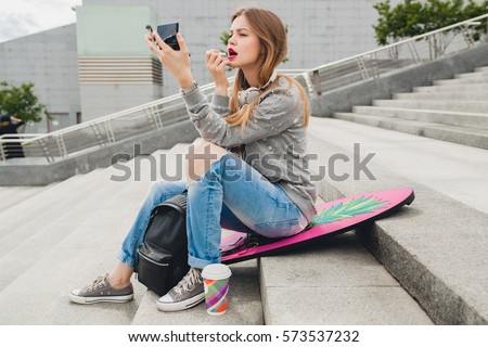 young smiling beautiful hipster happy woman sitting in city street, doing make-up, lipstick, mirror, spring trend, teenage style, balance board, jeans, sneakers