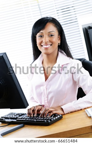 Young smiling black business woman at desk typing on computer