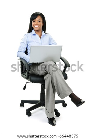 Young smiling black business woman sitting in leather office chair with laptop computer