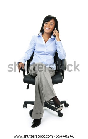 Young smiling black businesswoman on phone sitting in leather office chair