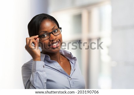Young smiling black woman holding her eyeglasses