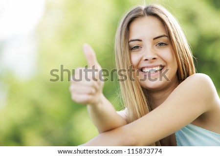 Young smiling blond female outdoors showing thumb up sign