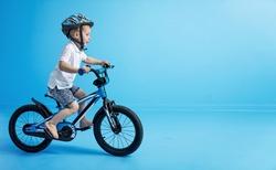 Young smiling boy riding a bike
