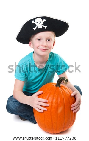 young smiling boy wearing pirate hat and holding pumpkin, isolated on white