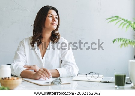 Young smiling brunette woman nutritionist plus size in white shirt working at laptop on table with house plant in the bright modern office Foto stock ©