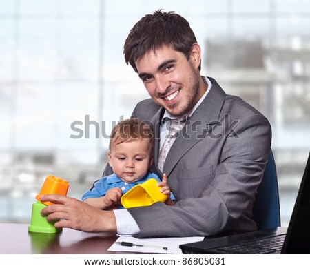 Young smiling business man holding his little baby son