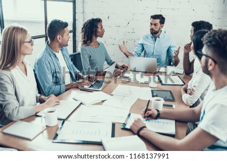 Young Smiling Business People on Meeting in Office. Group of Young Coworkers Sitting Together at Table in Modern Office. Business Team Working Together. Teamwork Concept. Corporate Lifestyle #1168137991