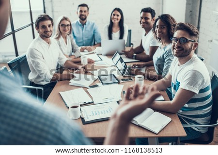 Young Smiling Business People on Meeting in Office. Group of Young Coworkers Sitting Together at Table in Modern Office and Listening to Businessman Presenting. Teamwork Concept. Corporate Lifestyle #1168138513