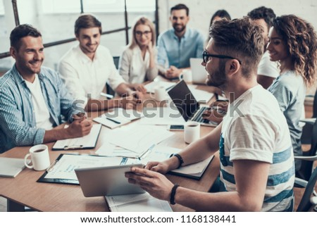Young Smiling Business People on Meeting in Office. Man showing Project on Tablet to Group of Young Happy Collegues Sitting Together at Table Working on Laptops in Modern Office. Teamwork Concept #1168138441