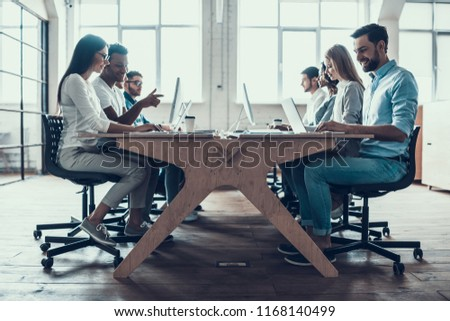 Young Smiling Business People Working on Laptops. Group of Young Coworkers Sitting Together at Table and Working on Laptops in Modern Office. Teamwork Concept. Corporate Lifestyle