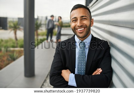 Young smiling business university student standing against college campus wall with arms crossed