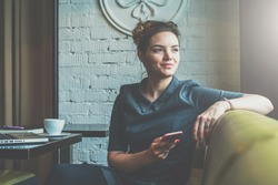 Young smiling business woman sitting in cafe at table, leaning his hand back in chair,looking out window and holding smartphone.On table is laptop, notebook and cup of coffee. Student learning online.
