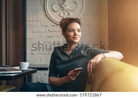 Young smiling business woman sitting in cafe at table, leaning his hand back in chair,looking out window and holding smartphone.On table is laptop, notebook and cup of coffee. Girl using gadget. #579721867