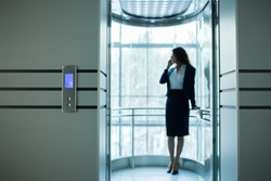Young smiling  business woman talking by phone in elevator