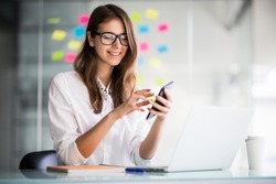 Young smiling business woman using smartphone near computer in office, copy space