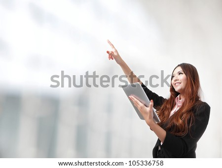 Young smiling business woman using tablet computer and hand finger point to empty copy space, model is a asian beauty