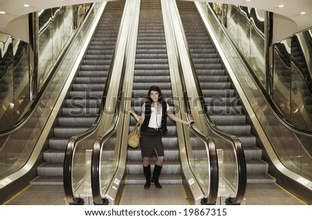 Young smiling business woman walking at escalator in some modern building.